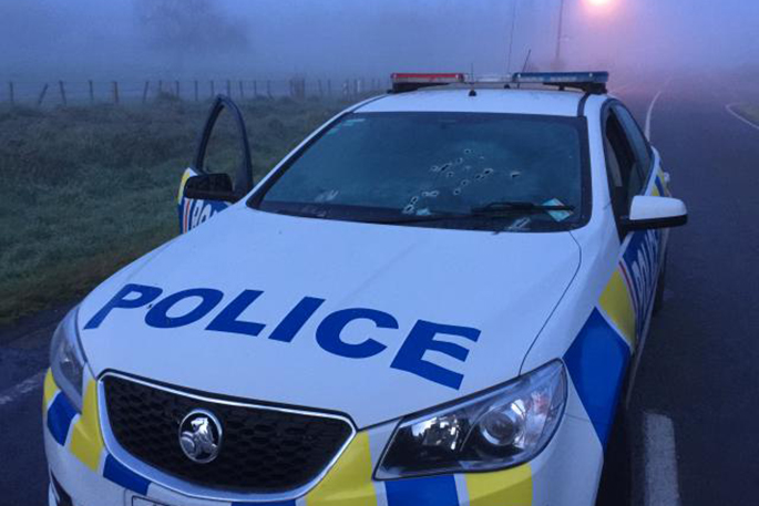 Police hunt gunman who fired on officers The bullet-riddled police car. Supplied